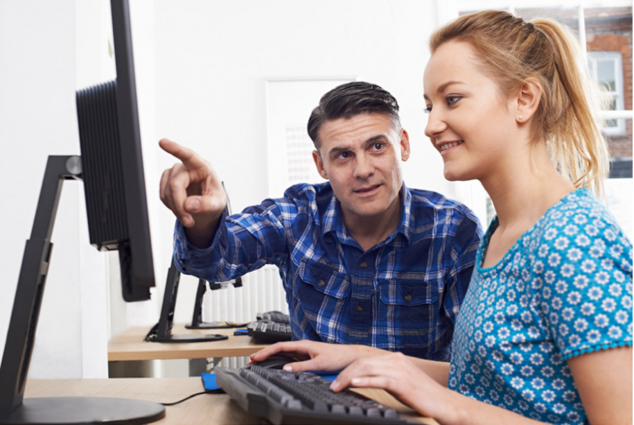 Image of a young girl working at a computer while a man points to something on the screen